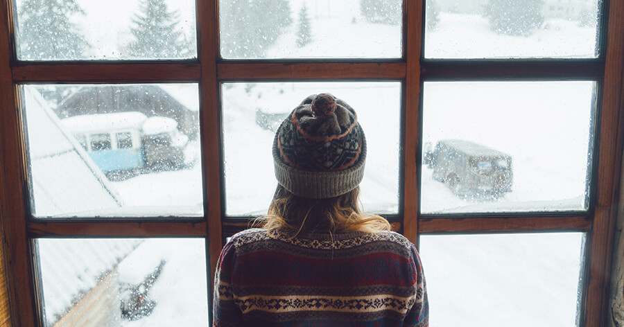 a lady standing in front of a window watching the snow outside the window