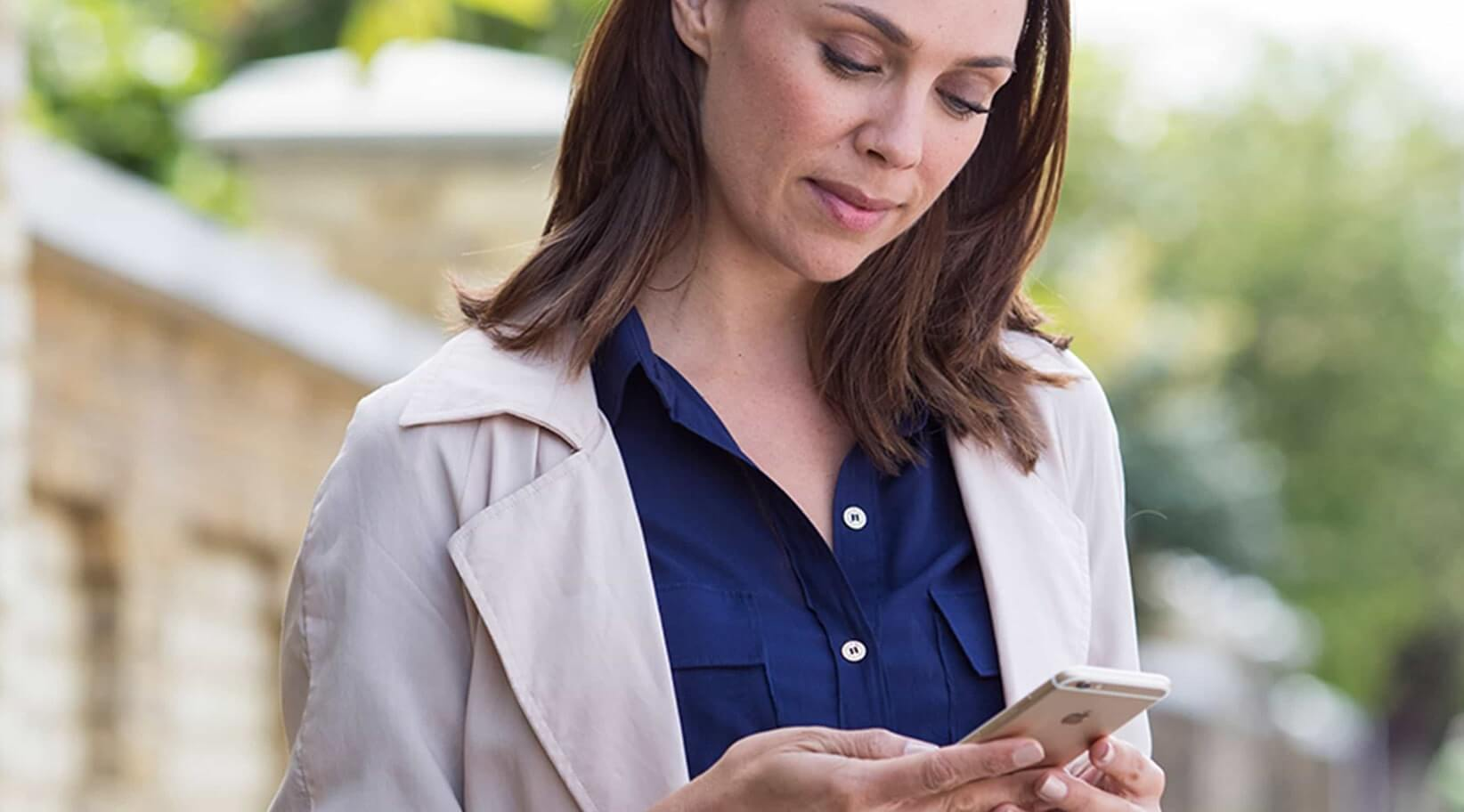 Woman reviewing energy savings from smart home on smart phone