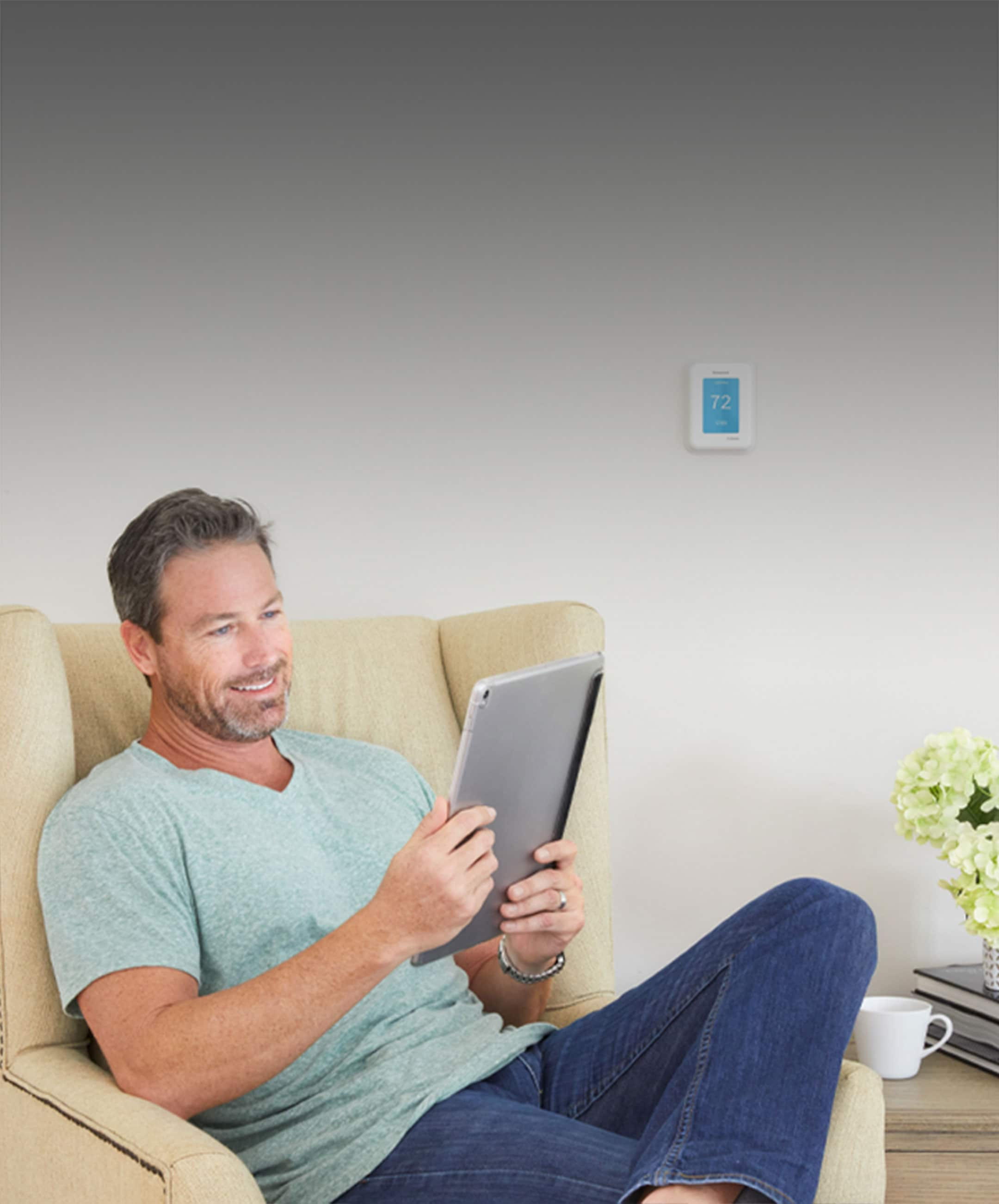 Man sitting in chair enjoying comfortable room controlled by smart thermostat